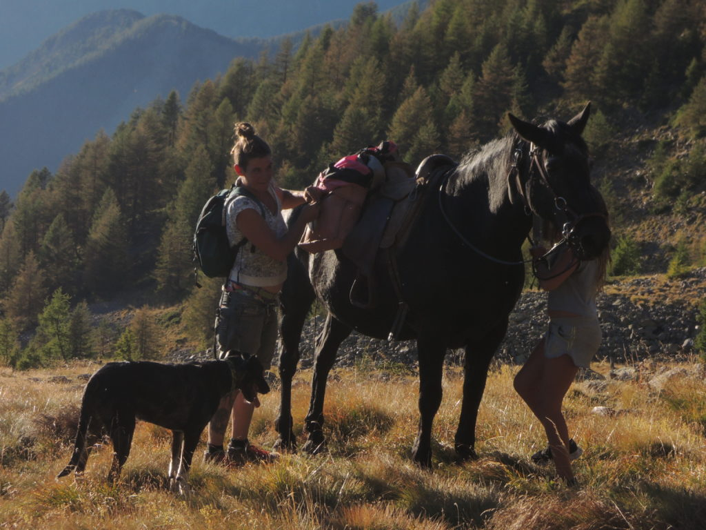 Katrin e Sarah sistemano l'equipaggiamento dei cavalli prima di affrontare la parte più selvaggia del sentiero che porta alla Vacherie in un'ora di boschi, rii e praterie